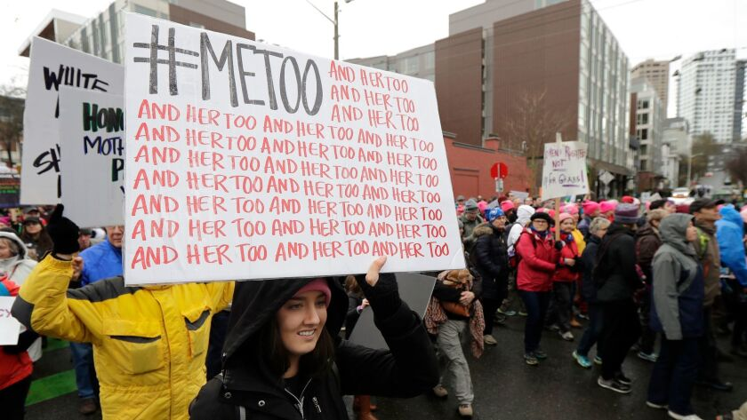A marcher carries a sign with the popular Twitter hashtag #MeToo used by people speaking out against