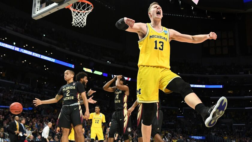Michigan's Moritz Wagner celebrates his basket after being fouled by a Florida St. player.