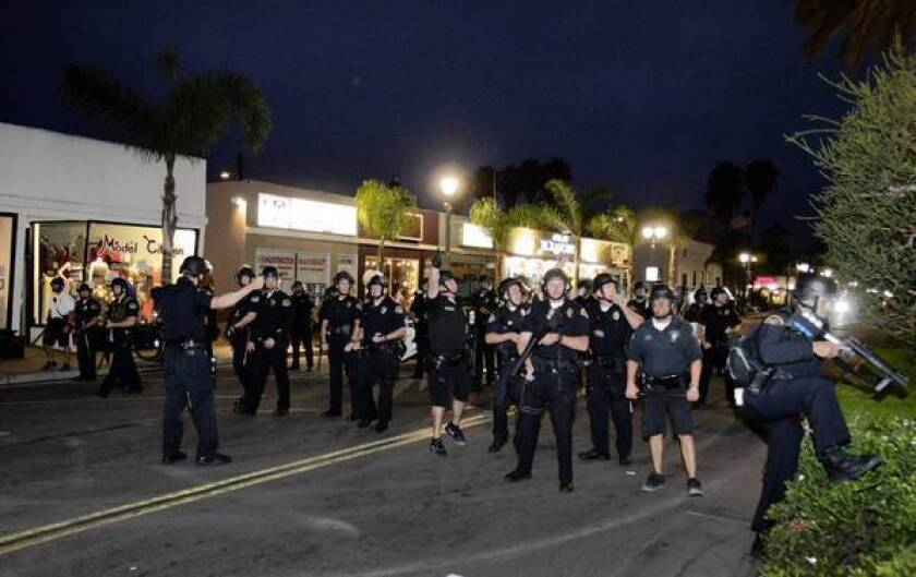 Police officers make a stand at Main Street to thwart looting and rioting in Huntington Beach on Sunday night.