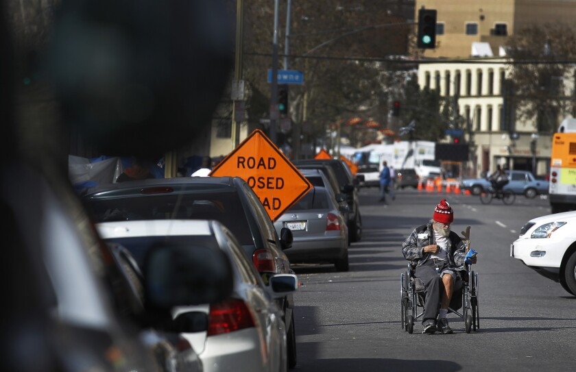 A man who said he was a Navy veteran pushes his wheelchair backward on skid row.