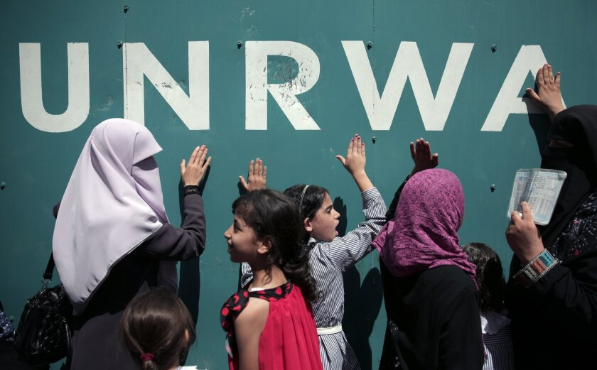 """Palestinians demonstrate against a U.N. Relief and Works Agency (UNRWA) funding gap that could keep about 500,000 Palestinian students out of school this fall, outside the UNRWA Gaza Headquarters in Gaza City, Sunday, Aug. 16, 2015. The deputy chief of the UNRWA, which operates 700 schools, Sandra Mitchell, said Monday that """"if funding does not arrive"""" this month, the agency could delay the start of the school year. (AP Photo/Khalil Hamra)"""
