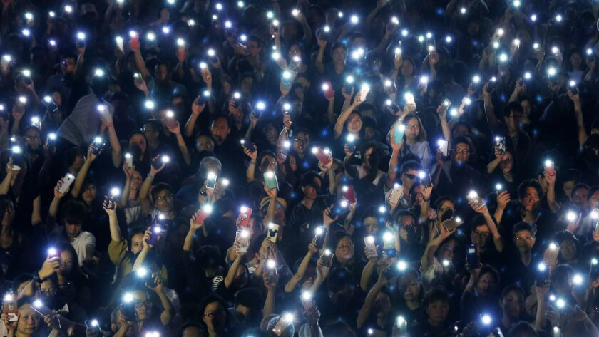Attendees hold up their lit mobile phones during a rally by mothers in Hong Kong on Friday, July 5,
