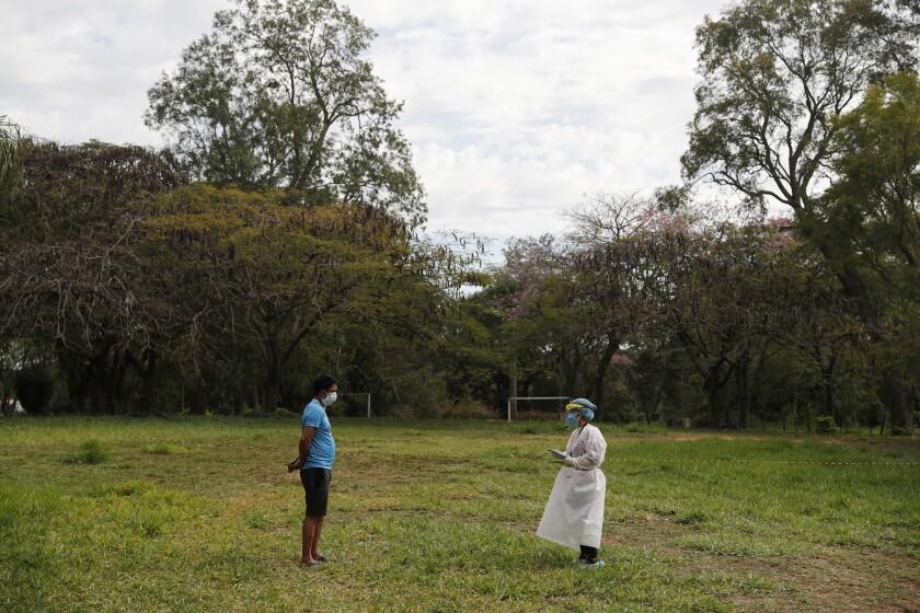Un hombre en cuarentena es entrevistado por un miembro del Mecanismo Nacional de Prevención de la Tortura (MNPT) durante una visita de la institución a una propiedad católica reconvertida en un albergue gestionado por el gobierno para que los ciudadanos que regresan al país pasen la cuarentena obligatoria de dos semanas y dos test consecutivos de COVID-19, como medida de preventiva contra la pandemia del coronavirus, cerca de Asunción, Paraguay, el 18 de junio de 2020. Además del relativo aislamiento de Paraguay, los expertos relacionan el éxito del país a la hora de controlar la propagación del COVID-19 con la creación de una red de centros de cuarentena en academias militares, hoteles e instituciones religiosas. (AP Foto/Jorge Sáenz)