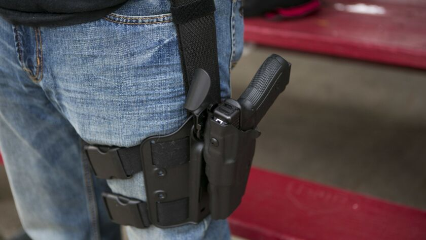 In this Tuesday Sept. 29, 2015 photo, Josh Tishhouse carries his Glock pistol at Gallup Park during