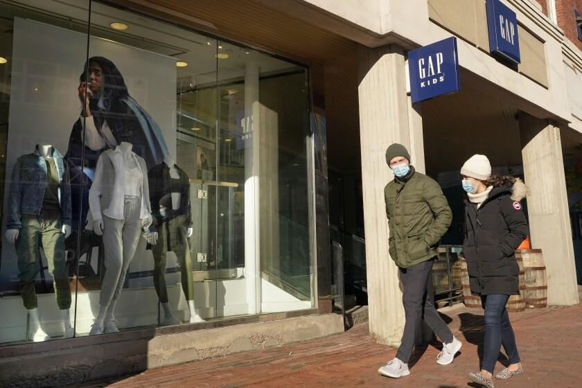 Dos personas caminan frente a una tienda de la cadena Gap el jueves 25 de febrero de 2021, en Cambridge, Massachusetts. (AP Foto/Steven Senne)