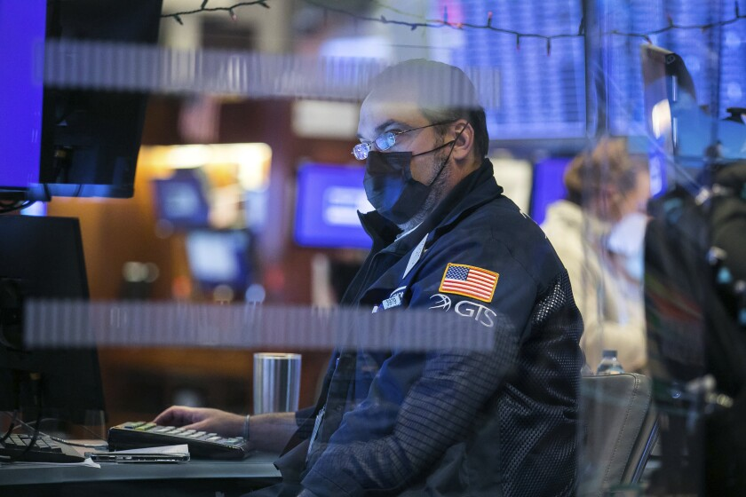 In this photo provided by the New York Stock Exchange, a specialist works at his post on the trading floor.