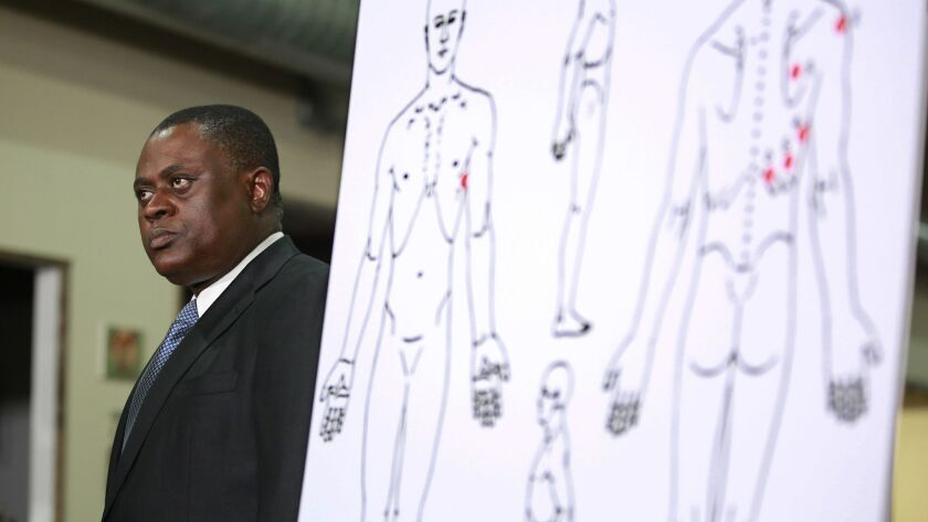 Pathologist, Dr. Bennet Omalu, stands next to a diagram showing where police shooting victim Stephon