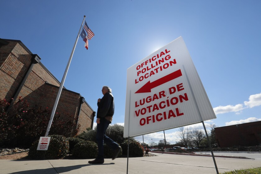 FILE - In this Feb. 26, 2020 file photo, using both the English and Spanish language, a sign points potential voters to an official polling location during early voting in Dallas. Getting enough people to staff polling places amid the coronavirus pandemic is a challenge in many states. The virus' disproportionate impact on Latinos has made the task of recruiting Spanish-speakers even more difficult. (AP Photo/LM Otero, File)