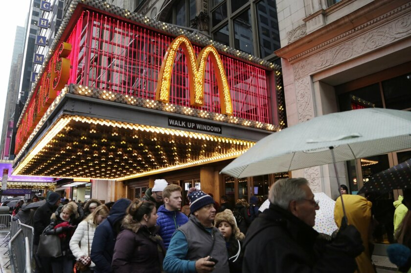 In this Tuesday, Dec. 29, 2015, photo, pedestrians pass under a McDonald's marquee in New York. McDonald's reports quarterly financial results, Monday, Jan. 25, 2016. (AP Photo/Mark Lennihan)