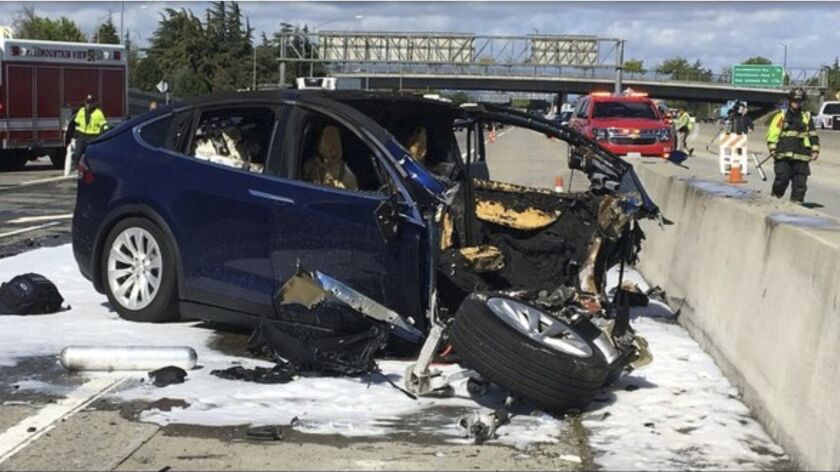 Emergency personnel work at the scene where a Tesla electric SUV crashed into a barrier on U.S. Highway 101 in Mountain View, Calif.