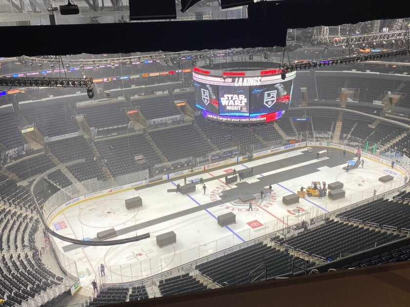 A crew works to change the basketball court to an ice hockey rink at Staples Center.