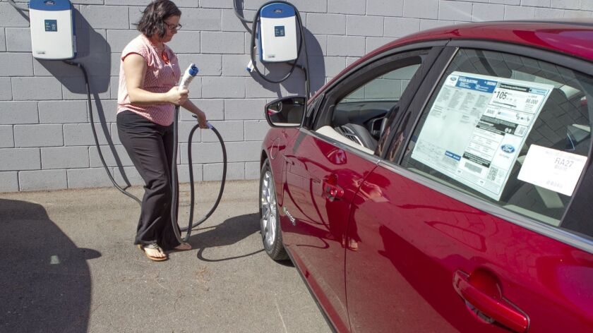 An El Cajon Ford employee connects a new electric vehicle to the charging station at the dealership.