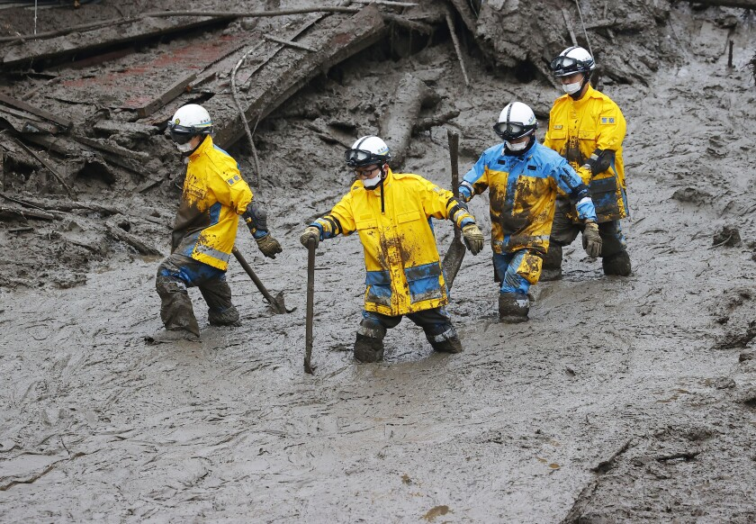Rescuers conduct a search operation at the site of a mudslide at Izusan in Atami, Shizuoka prefecture, southwest of Tokyo, Sunday, July 4, 2021. More than 1,000 soldiers, firefighters and police on Sunday waded through a giant mudslide that ripped through the resort town as it swept away houses and cars. (Kyodo News via AP)