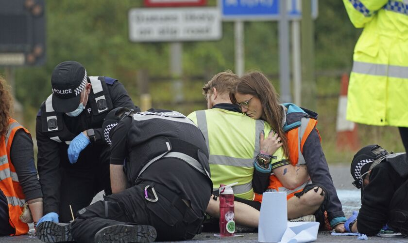 Police officers work to free protesters from Insulate Britain who had glued themselves to the highway, at a slip road at Junction 4 of the A1 motorway, near Hatfield, England, Monday, Sept. 20, 2021. Protesters are demonstrating for the government to insulate every home in Britain to tackle climate change and fuel poverty. (Steve Parsons/PA via AP)