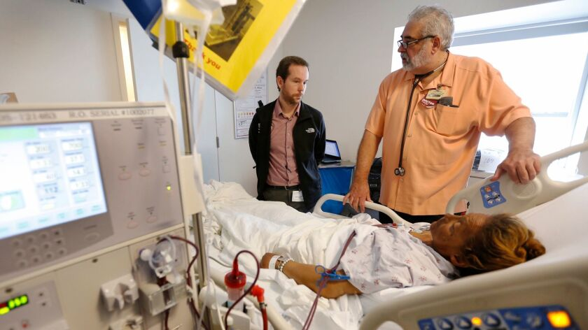 Dr. Jonathan LoPresti, right, a Los Angeles County USC Medical Center MD for 36 years with resident physician Michael Kendall, left, meet with a patient on March 17.