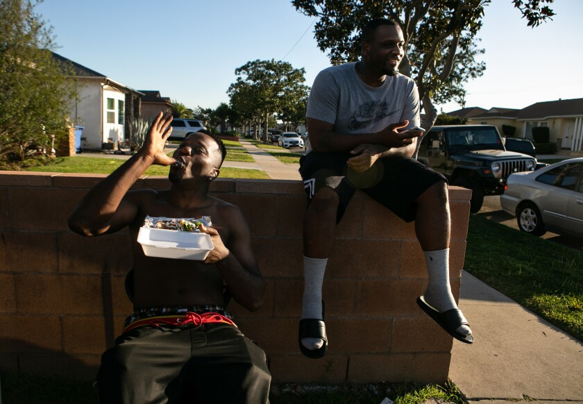 Lucius Johnson, left, enjoys his shrimp tacos while Davonte Gilmore waits for his order at Munchie Madness in Compton.