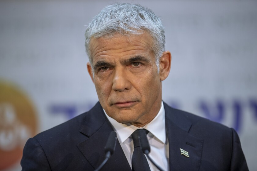 A closeup photo of Yair Lapid before a microphone