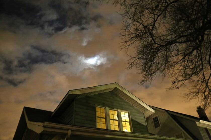 Photograph of a house at night with a cloudy sky.