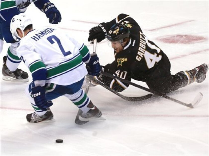 Dallas Stars center Ryan Garbutt (40) dives to make a shot on-goal as he is defended by Vancouver Canucks' Dan Hamhuis (2) during the first period of an NHL hockey game on Thursday, April 18, 2013, in Dallas. (AP Photo/ Michael Mulvey)