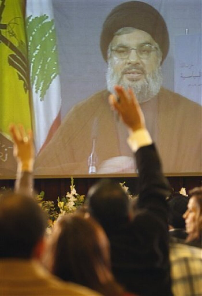 Hezbollah leader Sheik Hassan Nasrallah is seen speaking via a video link as journalists raise their hands to ask questions of  him during a press conference in which he read the group's new political manifesto, the second since Hezbollah was born in the early 1980s, in the southern suburb of Beiru