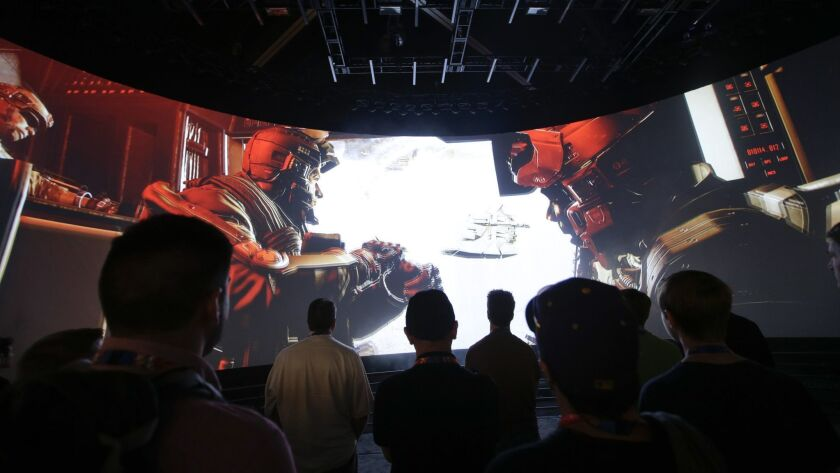 "FILE - In this June 12, 2014 file photo, people watch the ""Call of Duty: Advanced Warfare"" video gam"