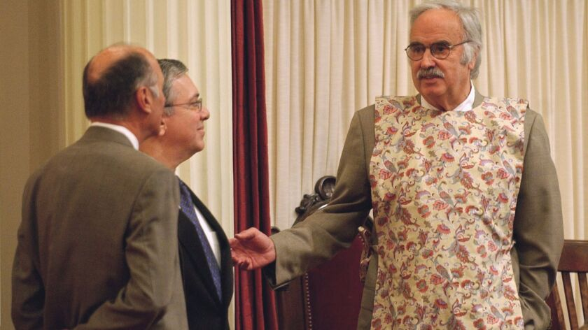 Wearing a kitchen apron to protest a pastor's remarks in 2004, then-Senate President Pro Tem John Burton, right, talks with Senate Minority Leader Dick Ackerman, R–Fullerton, center, and Sen. Charles Poochigian, R–Fresno.