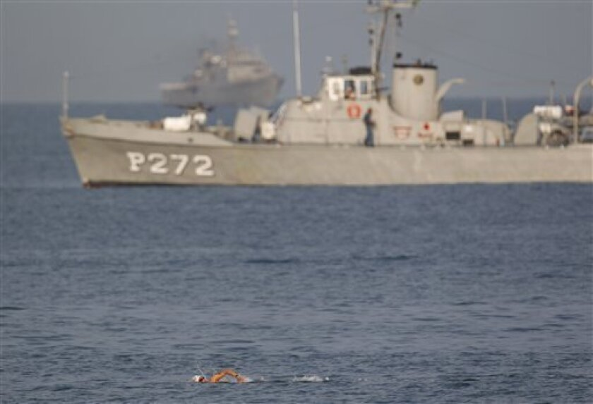 Backdropped by Mexican Navy ships securing the area, Canada's Richard Weinberger begins his swim in the men's 10km open water swimming race at the Pan American Games in Puerto Vallarta, Mexico, Saturday Oct. 22, 2011. (AP Photo/Eduardo Verdugo)