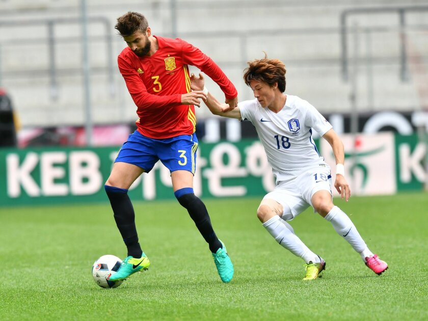 Spain's Gerard Pique, left, challenges for the ball with South Korea's  Hwang  Ui-jo during a friendly soccer match between Spain and South Korea in Salzburg, Austria, Wednesday, June 1, 2016. The Spain National Football Team is in Austria for a training camp in preparation for the  EURO 2016 socce