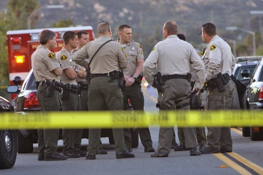 Sheriff's deputies gather Sunday near a Poway home after deputies called to the scene reportedly shot and killed an armed man.