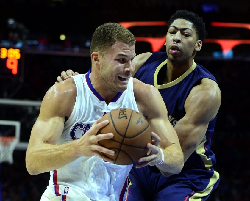 Blake Griffin, left, drives against Anthony Davis in a game between the Clippers and the New Orleans Pelicans at Staples Center in Los Angeles.