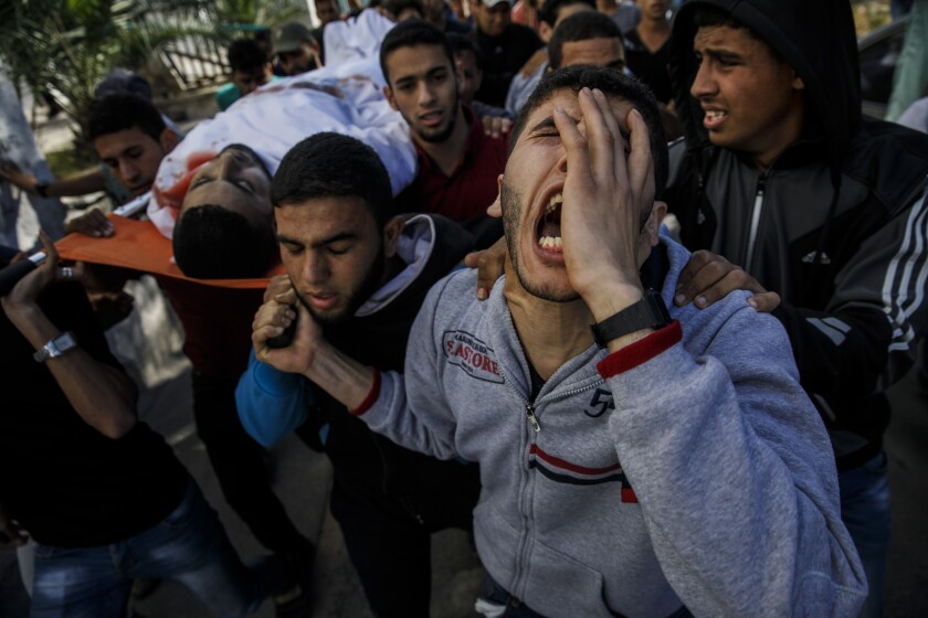 GAZA CITY, GAZA -- MONDAY, MAY 14, 2018: Relatives of Taher Ahmed Madi, 25, carry his body from the