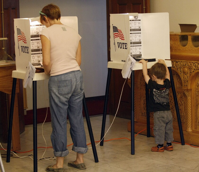 A mom gives her son a preview of the voting process during the Los Angeles municipal primary election on May 21, 2013.