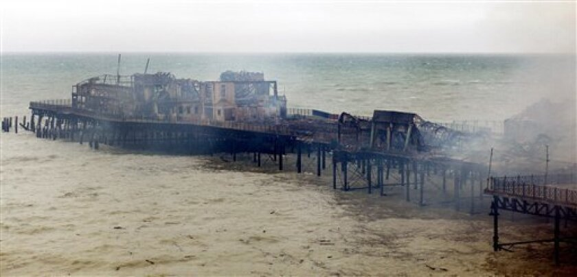 Hastings Pier in Hastings, southern England smolders after a fire early Tuesday Oct. 5, 2010. Two people were arrested on suspicion of arson after the Victorian pier was severely damaged by fire. The blaze destroyed 95 percent of Hastings pier. (AP Photo/Gareth FullerPA Wire)