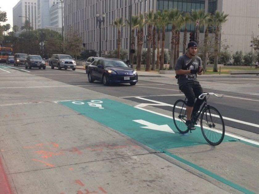 A bicyclist rides the new darker green bike lane on Spring Street south of 2nd Street in downtown Los Angeles.