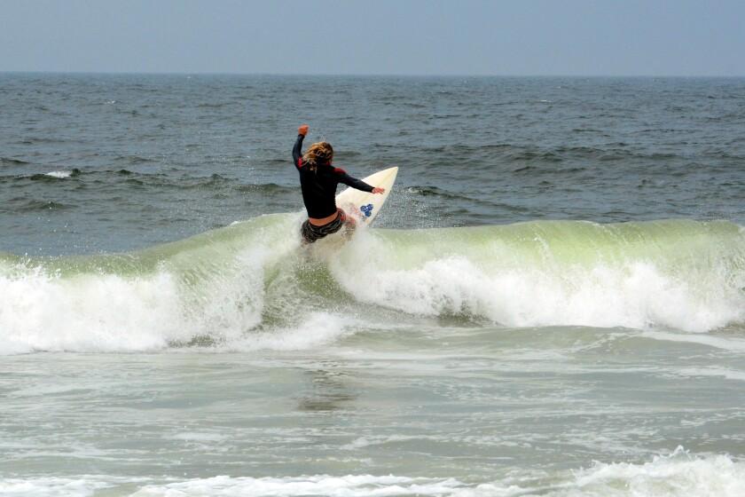 A surfer rides a wave near Casino Pier.