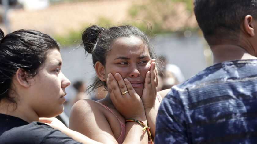 A student cries outside after a deadly attack on the Raul Brasil state school in Suzano, in Brazil's greater Sao Paulo area, on March 13, 2019.