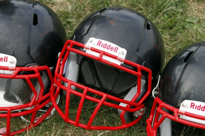 FILE - In this Aug. 4, 2012, file photo, Riddell football helmets that were given to a group of youth football players from the Akron Parents Pee Wee Football League are shown in Akron, Ohio. Seven football organizations are about to receive equipment from helmet manufacturer Riddell through the co