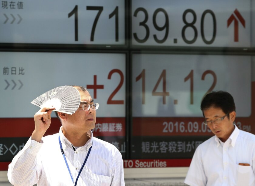 People walk by an electronic stock board of a securities firm in Tokyo, Monday, Sept. 5, 2016. Asian stocks rose Monday as a U.S. jobs report set off hopes among traders that the Federal Reserve will wait before raising interest rates. (AP Photo/Koji Sasahara)