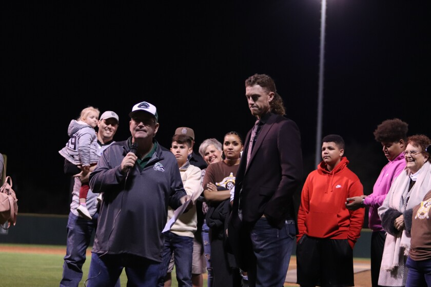 Brad Cone, the radio announcer for Cedar Park High School baseball, introduces Chris Paddack at a ceremony retiring Paddack's high school jersey on Jan. 31. Paddack's family looks on from behind.