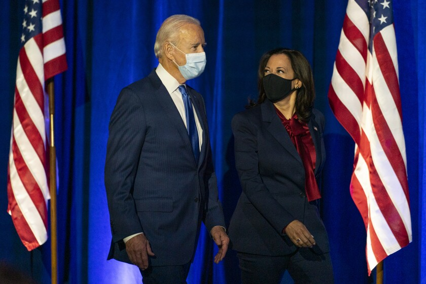 Joe Biden and Kamala Harris walk onto a stage in front of a blue curtain and two U.S. flags