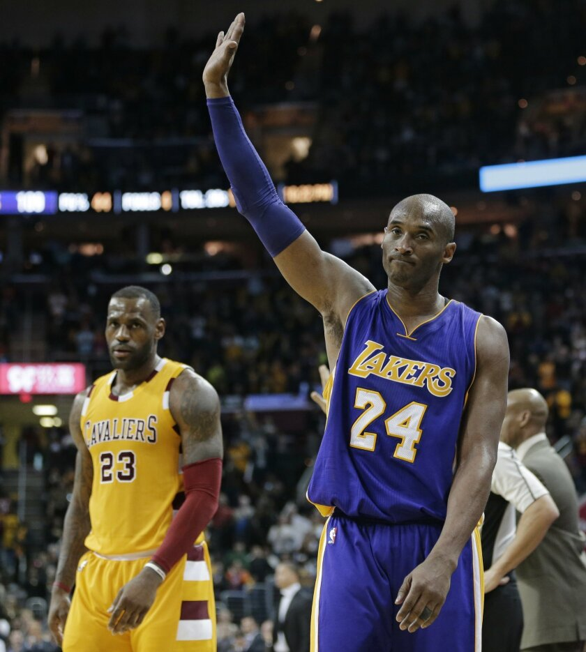 Los Angeles Lakers' Kobe Bryant, right, waves to the crowd as he leaves the game in the second half of an NBA basketball game Wednesday, Feb. 10, 2016, in Cleveland. LeBron James, left, watches. The Cavaliers won 120-111. (AP Photo/Tony Dejak)