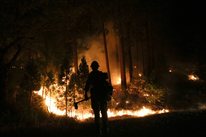 A firefighter watches the Rim fire near Yosemite National Park. The long-burning blaze, which began in mid-August, was a high-profile exception to an otherwise quiet fire season.