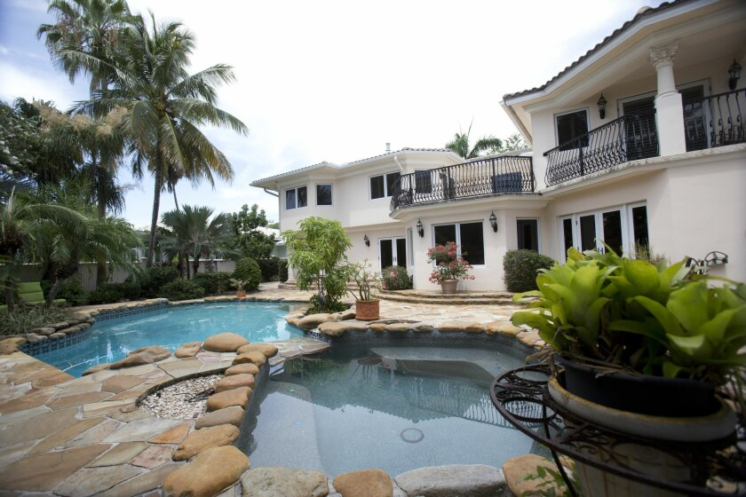 FILE - This July 22, 2015 file photo shows the back yard and pool area of the five-bedroom Florida mansion belonging to 1970's heartthrob David Cassidy in Fort Lauderdale, Fla. The home has sold for just over $2 million. Fisher Auction Co. spokesman Ryan Julison said a bankruptcy court approved the sale Friday, Sept. 25. The sale of the 7,000-square-foot waterfront home should close within 30 days. The 65-year-old Cassidy filed a Chapter 11 bankruptcy case earlier this year. (AP Photo/Wilfredo Lee, File)