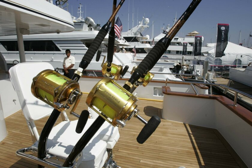A sportfishing fighting chair, decked out with fishing poles, was on display on one of the yachts for sale yesterday at Shelter Island Marina. (John Gibbins / Union-Tribune)