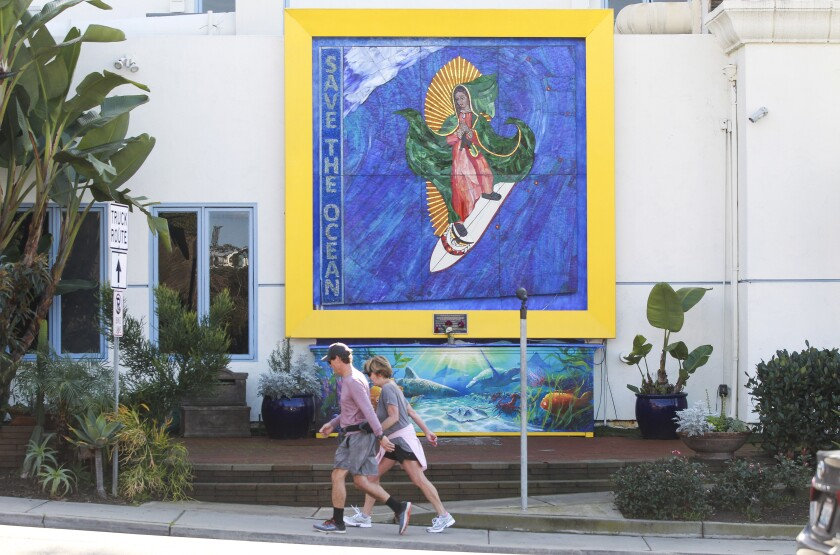 "Pedestrians walk past the ""Surfing Madonna"" mosaic displayed on Encinitas Boulevard on December 24, 2019 in Encinitas."