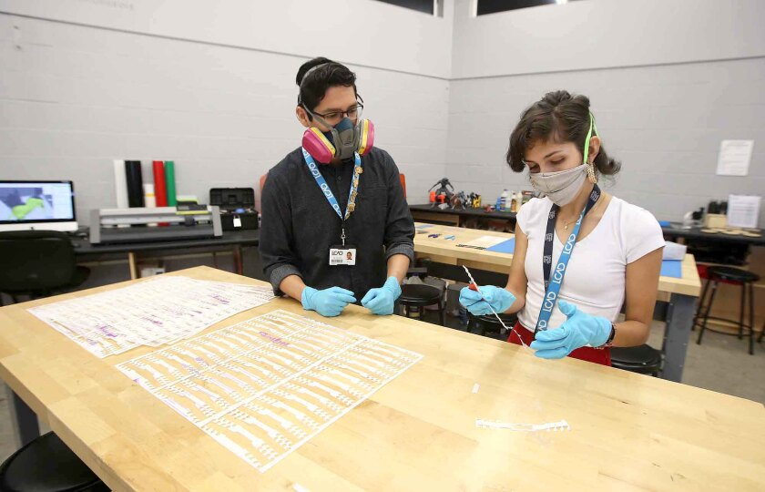 Fabrication lab director Hugo Hernandez, left, shows Elisa Gimenez how to cut out ear saver clips in the Laguna College of Art and Design lab on Wednesday.