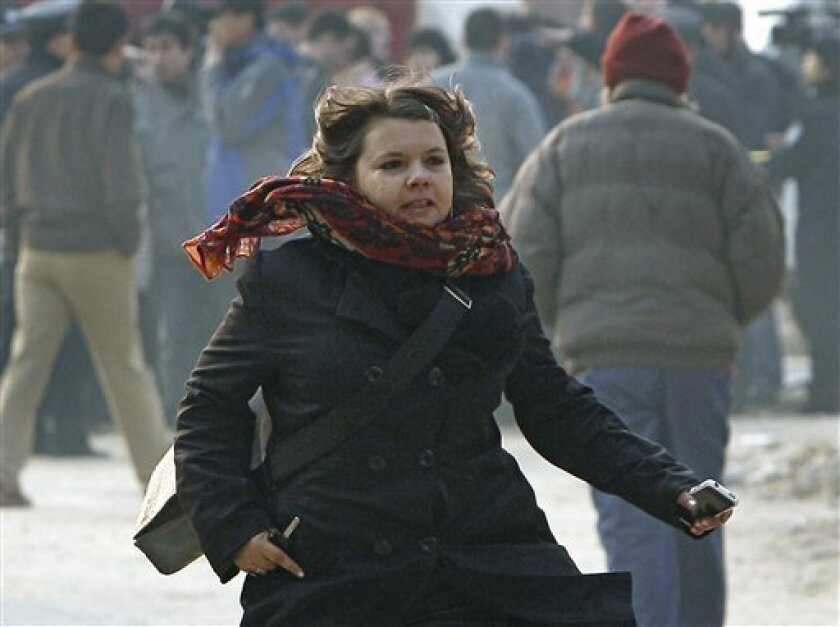 Karen Patterson of Canada, wife of Chinese artist Wu Yuren, runs past the crowd as she arrives for her husband's trial at the Wenyuhe Court in Beijing, China Wednesday, Nov. 17, 2010. Wu was detained and charged after he helped organize protests near Tiananmen Square against some urban development