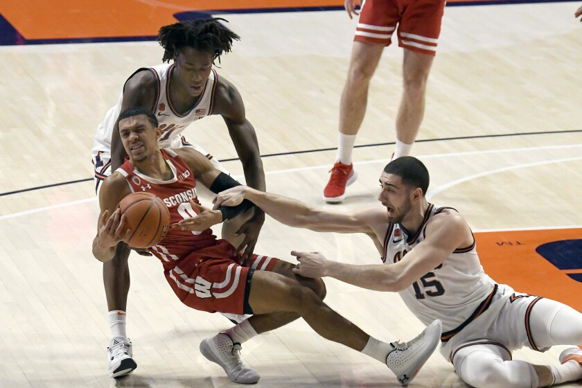 Wisconsin's guard D'Mitrik Trice (0) battles for ball control with Illinois guard Ayo Dosunmu and forward Giorgi Bezhanishvili (15) in the first half of an NCAA college basketball game, Saturday, Feb. 6, 2021, in Champaign, Ill. (AP Photo/Holly Hart)