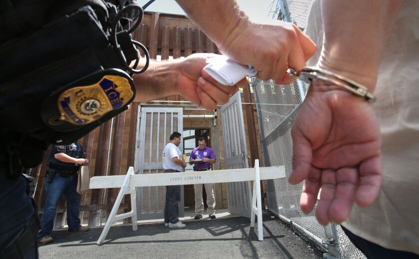 An Immigration and Customs Enforcement agent releases the handcuffs on a woman being deported to Mexico via Tijuana on May 24, 2016.