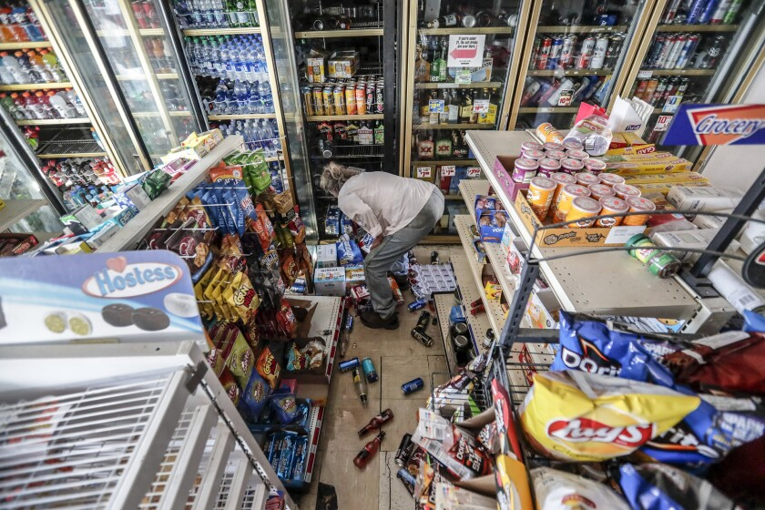 A customer rummages for a six-pack of beer at a damaged market in Trona, Calif., the day after a 7.1 earthquake.